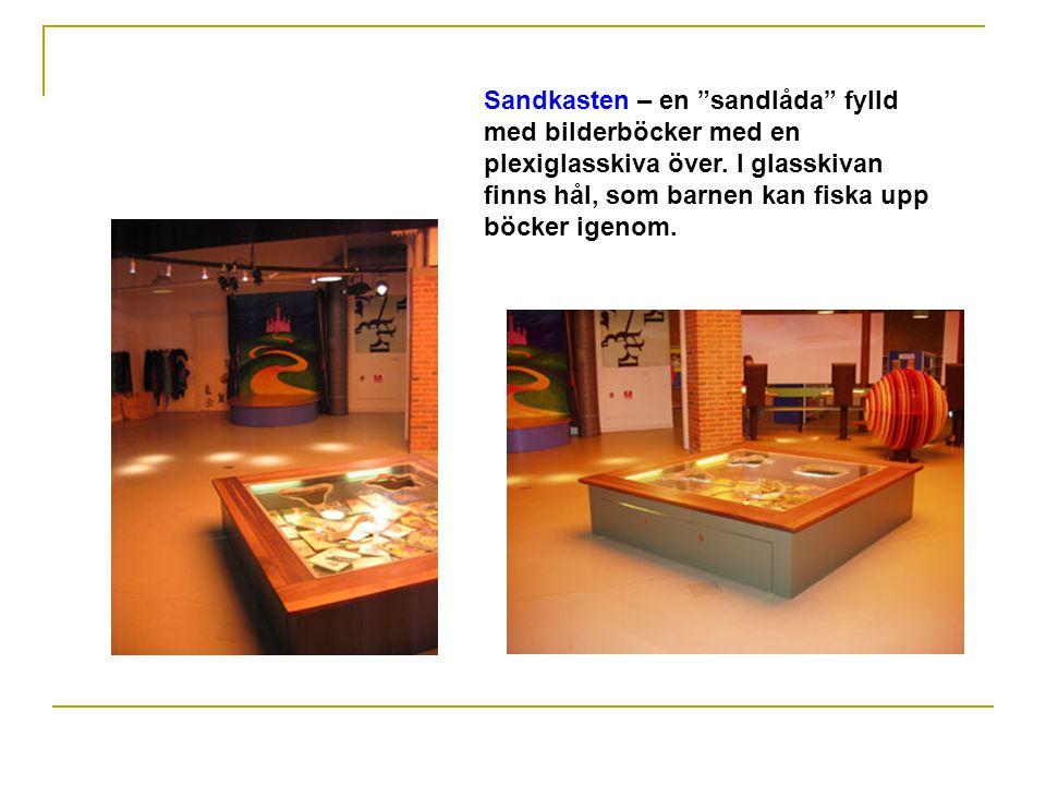 Sandkasten – en sandlåda fylld med bilderböcker med en plexiglasskiva över.