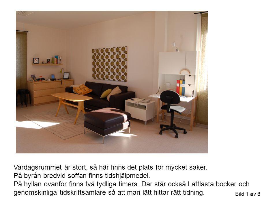 Bild 1 av 8 Vardagsrummet är stort, så här finns det plats för mycket saker. På byrån bredvid soffan finns tidshjälpmedel. På hyllan ovanför finns två