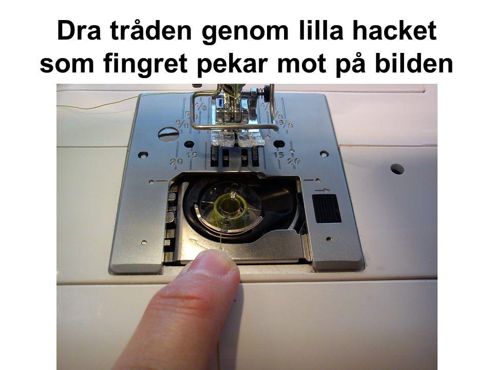 Dra tråden genom lilla hacket som fingret pekar mot på bilden
