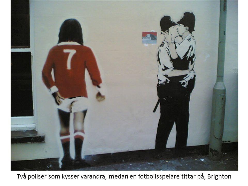 Två poliser som kysser varandra, medan en fotbollsspelare tittar på, Brighton