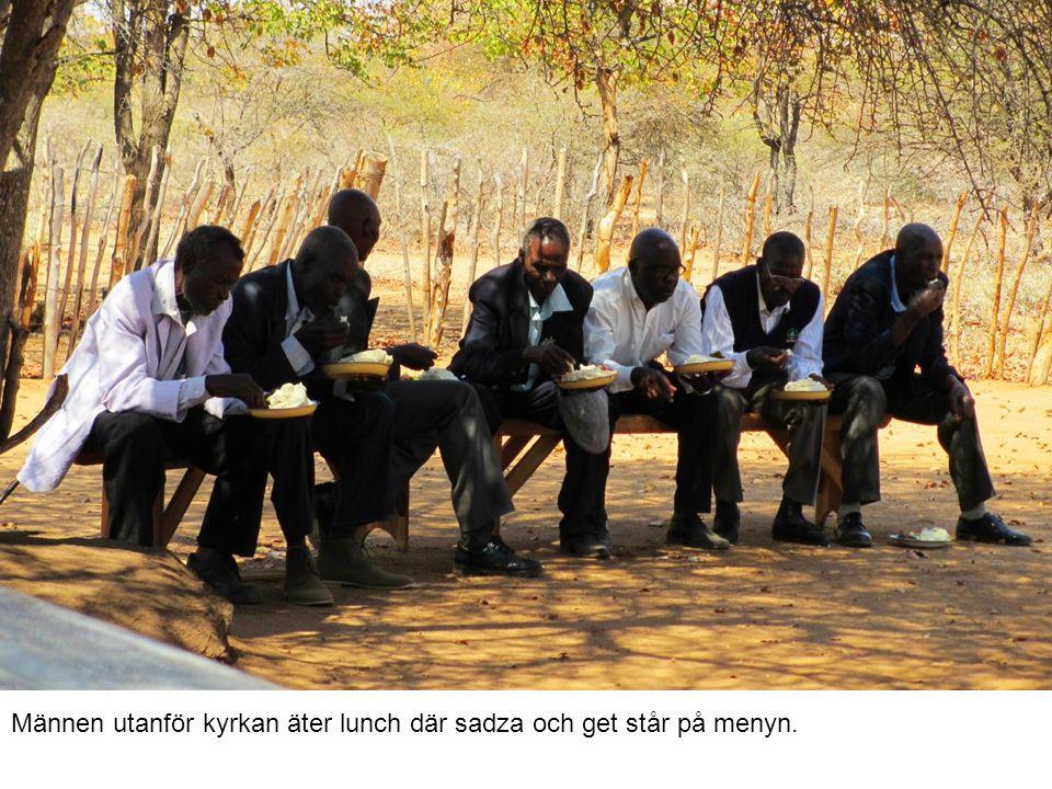 Männen utanför kyrkan äter lunch där sadza och get står på menyn.