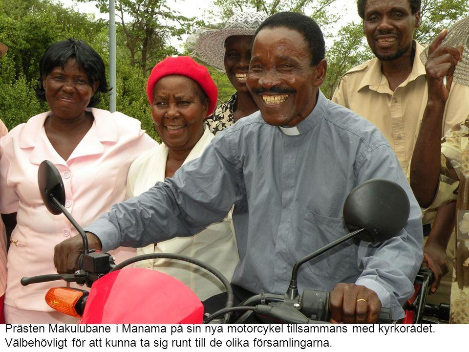 Prästen Makulubane i Manama på sin nya motorcykel tillsammans med kyrkorådet.