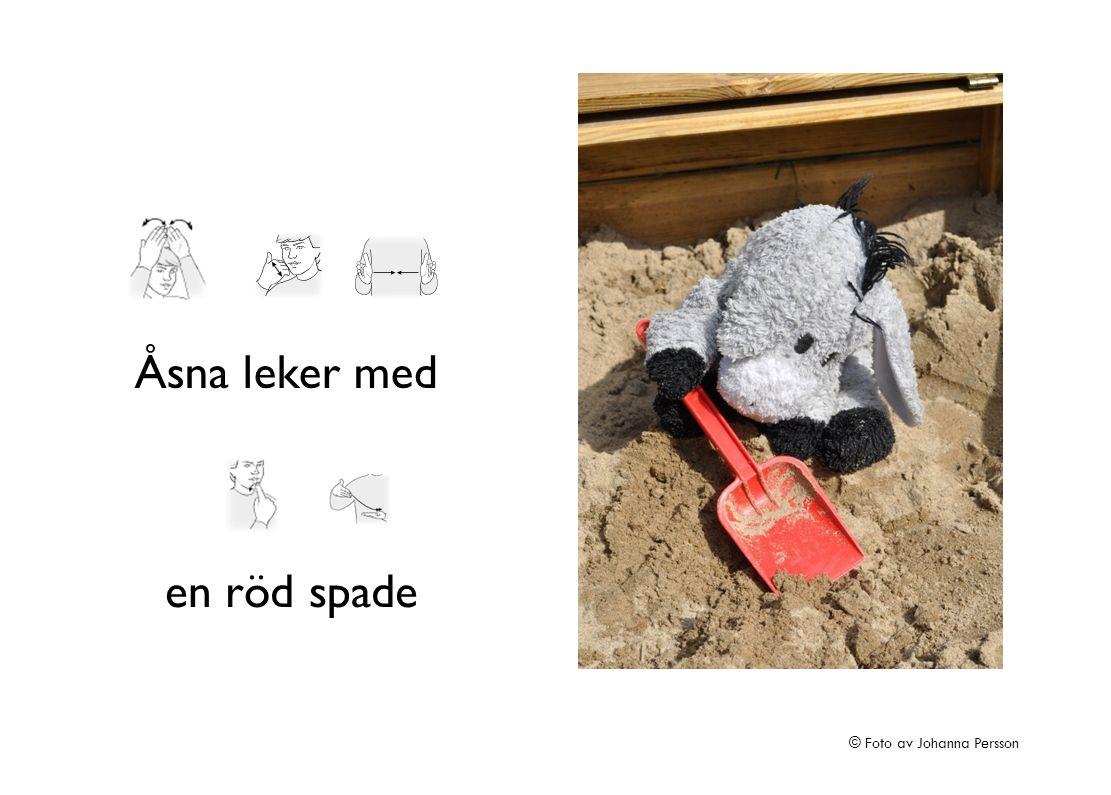 Åsna leker med en röd spade © Foto av Johanna Persson