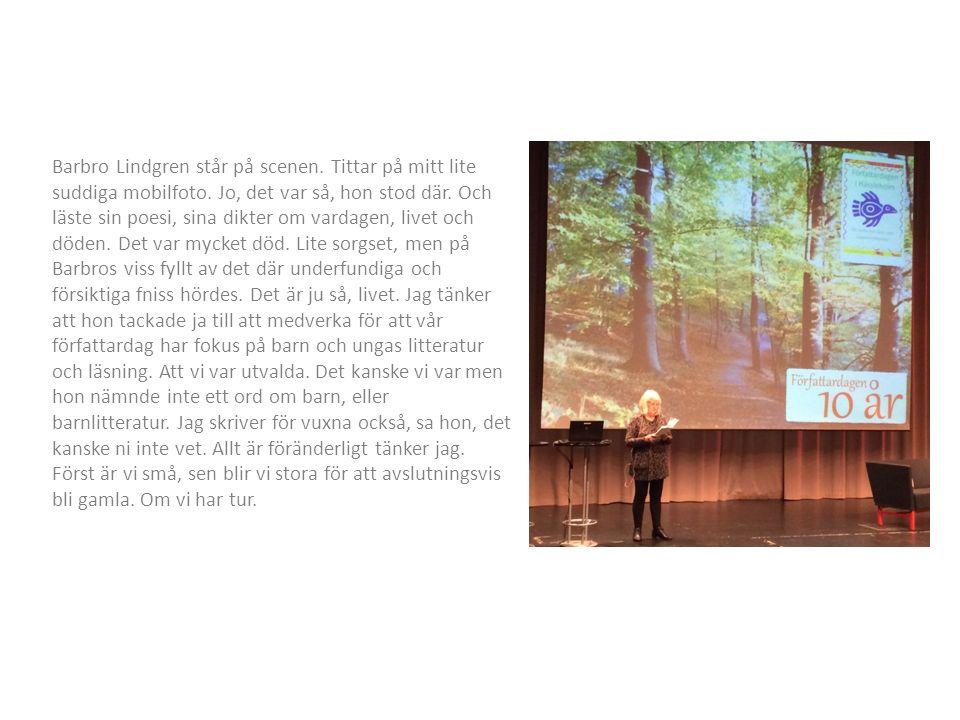 Barbro Lindgren står på scenen. Tittar på mitt lite suddiga mobilfoto.