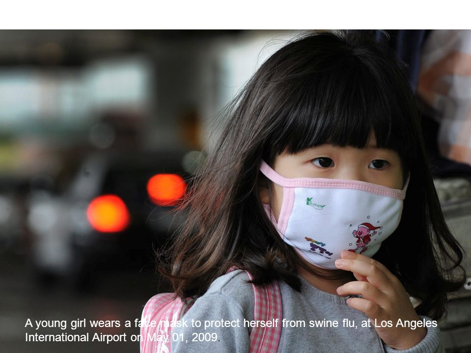 Bo-Eric Malmvall 2009 A young girl wears a face mask to protect herself from swine flu, at Los Angeles International Airport on May 01, 2009.