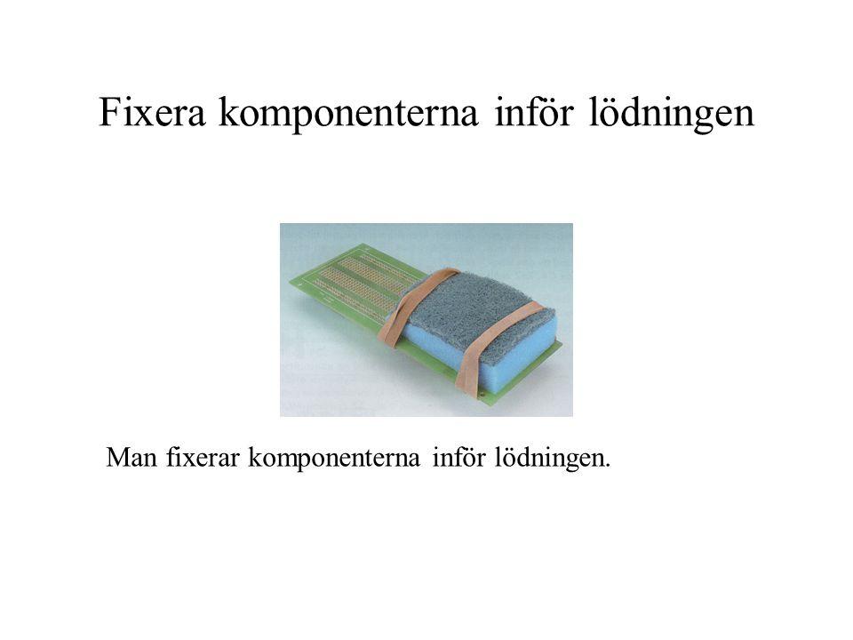Fixera komponenterna inför lödningen Man fixerar komponenterna inför lödningen.