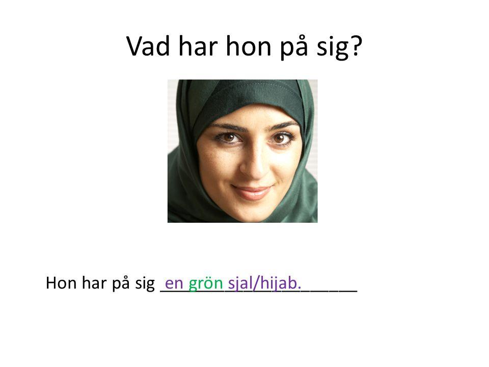 Vad har hon på sig? Hon har på sig _____________________en grön sjal/hijab.