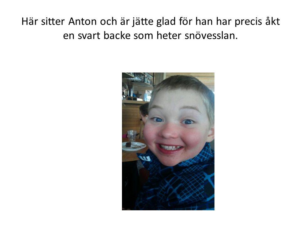 Här sitter Anton och är jätte glad för han har precis åkt en svart backe som heter snövesslan.