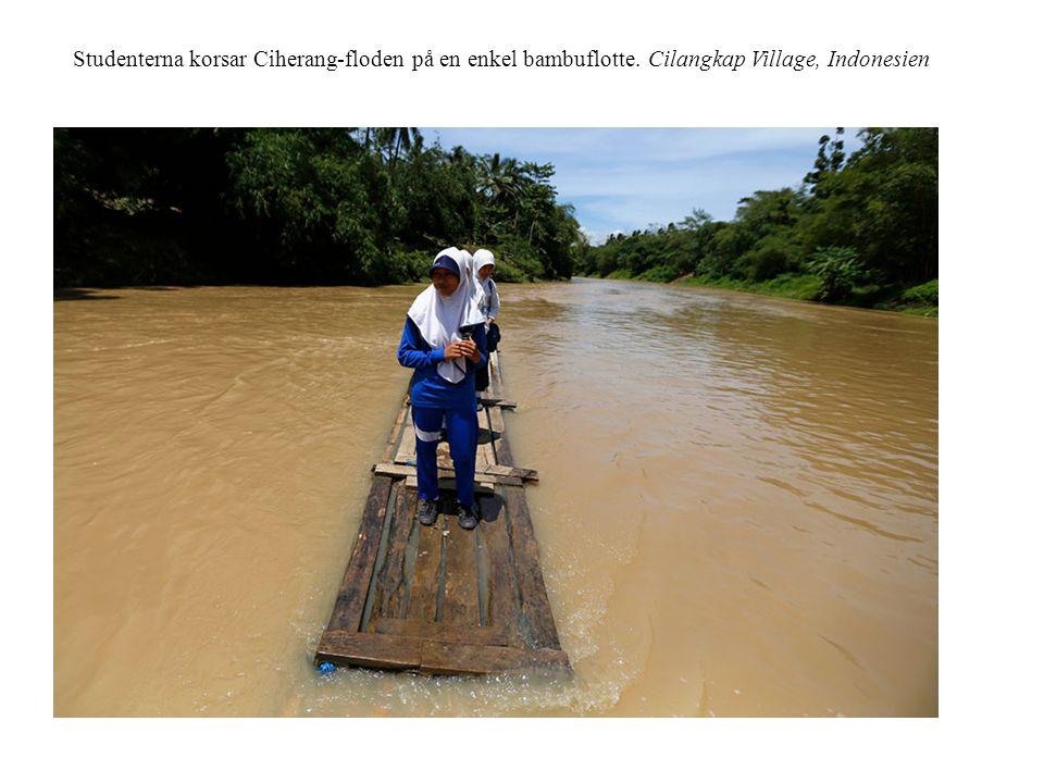 Studenterna korsar Ciherang-floden på en enkel bambuflotte. Cilangkap Village, Indonesien